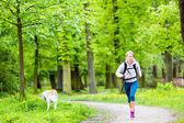 Woman runner walking with dog in summer park — Stok fotoğraf