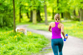 Woman runner running jogging in summer park — Stok fotoğraf