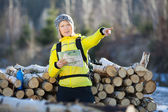 Woman hiking in winter forest with map — Stock Photo