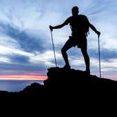 Man hiking silhouette in mountains, ocean and sunset — Stock Photo