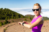 Woman trail runner looking at sport watch — Stock Photo