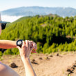 Cross country runner looking at sport watch — Stock Photo