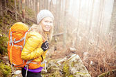 Woman hiking in autumn forest trail — Stock Photo