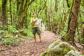 Hiker trekking with map in forest — Stock Photo
