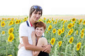 A young couple in a field of sunflowers — Stock Photo