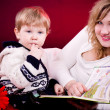 Mother and baby boy reading book and smiling on red background — Stock Photo #12368740