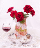 Bouquet of red roses with a glass of wine — Stock Photo