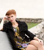 Hermosa mujer sentada en un banco — Foto de Stock