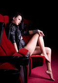 Sexy brunette poses on the red chair cinema — Stock Photo