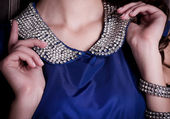 Luxury female collar with gems on blue dress — Stock Photo