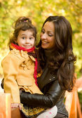 Happy mother and daughter in the autumn park — Stock Photo