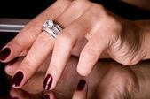 La main avec des bijoux doré sur fond noir — Photo