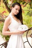 Beautiful bride with stylish make-up in white dress — Stock Photo