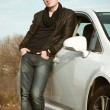 Attractive young man standing by car — Stock Photo