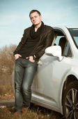 Attractive young man standing by car — Stockfoto