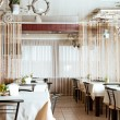 Interior of modern restaurant with the covered tables, wooden furniture — Стоковая фотография