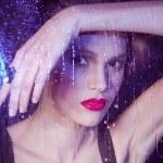 Girl watching through the rainy window — Stock Photo