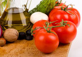Olive oil and tomatoes and other vegetables on a white background — Stock Photo