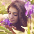 Young woman near blossoming iris flowers. Summer garden. — Stock Photo