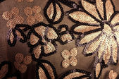 Flowers embroidered with sequins on a brown background — Stock Photo