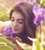 Young woman near blossoming iris flowers. Summer garden. — Stock Photo