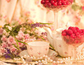 Vintage elegant cup, flowers and raspberry — Stock Photo