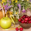 Field flowers,green apple and cherries in a plate — Stock Photo