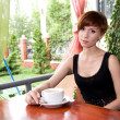 Portrait of beautiful young woman drinking coffee in restaurant — Stock Photo