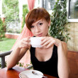 Portrait of beautiful young woman drinking coffee in restaurant — Stok fotoğraf