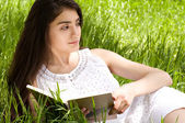 Beautiful woman in spring garden reading a book — Stock Photo
