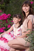 Happy family, young beautiful mother and her little daughter in the garden — Stock Photo