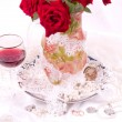 Beautiful red roses in vase with wine glass — Stock Photo