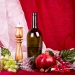 Beautiful composition with wine, grape, pomegranate on red background — Stock Photo