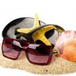 Beautiful exotic shell, shoe and glasses on sand — Stock Photo