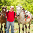 Handsome smiling man with horses in the forest — Stock Photo