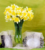 Beautiful spring flowers in a glass vase and frame on background — Stock Photo