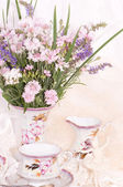 Vintage teacups, ballet dancer statuette, frame and flowers — Stock Photo