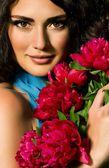 Visage de la beauté de la jeune femme avec fleurs rouges — Photo