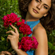 Beauty face of the young woman with red flowers — Stock Photo