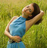 Beautiful woman in green grass — Stock Photo