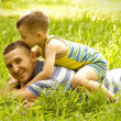 Father and son playing on green field — Stock Photo
