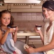 Young beautiful mother drinking coffee with her daughter — Stock Photo