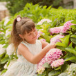 Happy beautiful girl smells flowers — Stock Photo
