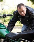 Muž stojící motocykl — Stock fotografie