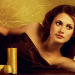 Beauty spa woman with golden candles — Stock Photo