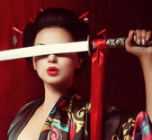 Beautiful geisha in kimono with samurai sword — Stock Photo