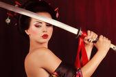 Beautiful geisha in kimono with samurai sword — Stock Photo