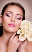 Beauty face of the young woman with flowers — Stock Photo
