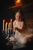 Little girl in dress with candlestick — Stock Photo