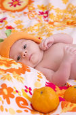 Newborn baby girl in orange hat with mandarin — Stock Photo